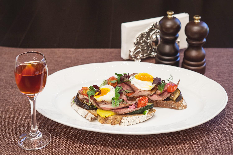 Бутерброд с телятиной, яйцом пашот, свекольным хреном и овощами на гриле, 480 р., и домашняя кедровая настойка, 350 р. за порцию