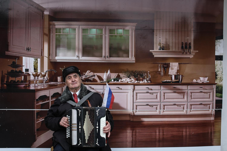 Сторонник объединения с Россией у плаката рекламы кухонь. Он, наравне с ополчением и русскими войсками, дежурит у штаба Военно-морских сил Украины в Севастополе
