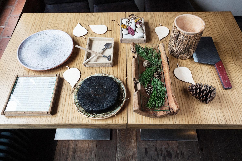 Квадрат из сосны с бортом (справа внизу), фирменная глиняная тарелка (слева вверху), ящик из березы с лопаткой и граблями (в центре вверху), спил с топором (справа), половина полена с хвоей и еловыми шишками (внизу справа), обугленный спил липы (внизу)