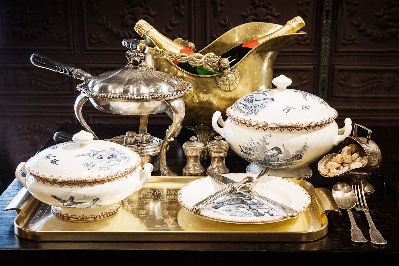 Сервиз с дроздами (две супницы, тарелка), горелка (слева), поднос из латуни, шлем-ведро, приборы для дичи (лежат на тарелке)