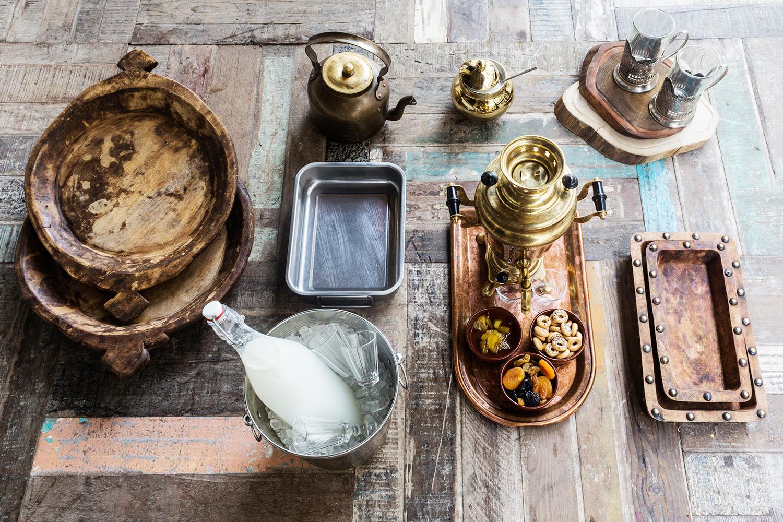 Большие деревянные подносы (слева вверху), старинный самовар и чайник, позолоченная сахарница, срезы из африканского тика (справа вверху), деревянные лотки с медными гвоздями (справа внизу), металлический лоток (в центре), литровая бутыль в ведерке (в центре внизу)